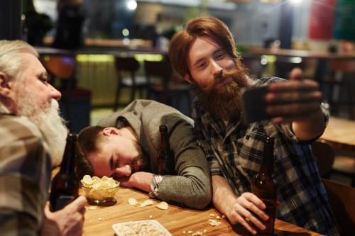 man taking selfie with passed out drunk in a bar